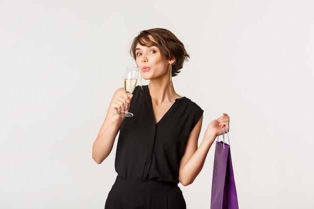 매력적인 유행 여자 샴페인을 마시 며 흰색 위에 서 공식적인 파티에 선물 상자를 들고.