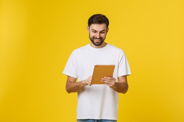 Attractive fashionable young caucasian man working on touch pad pc, making presentation, using wireless high speed internet connection