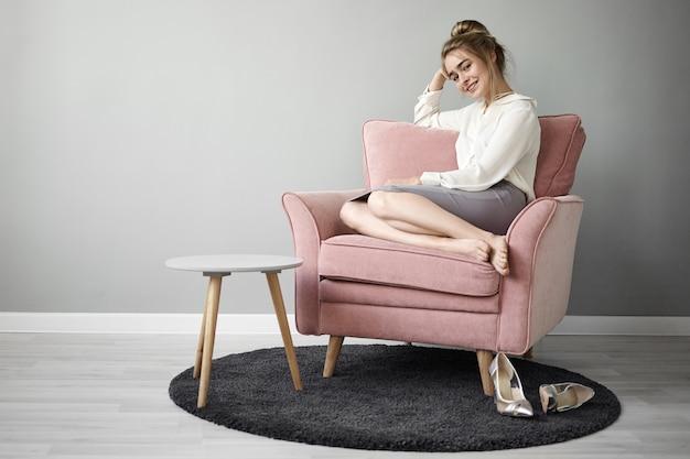 Привлекательная модная молодая европейская женщина с пучком волос и босыми ногами удобно сидит в розоватом кресле и улыбается, наслаждаясь свободным временем самостоятельно, в стильных туфлях на высоких каблуках на ковре