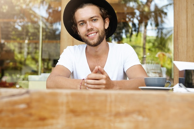 Attractive fashionable young man in trendy headwear sitting at wooden table of coffee shop