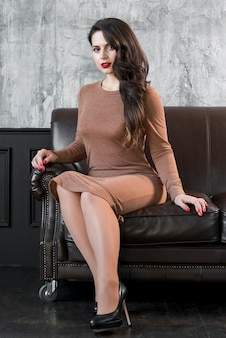An attractive fashionable young woman sitting on sofa looking at camera