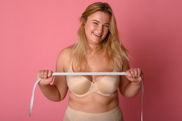 Привлекательная толстая девушка с рулеткой на розовом