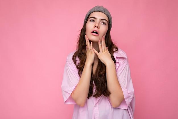 Привлекательная усталость исчерпала молодую кудрявую брюнетку в розовой рубашке и серой шляпе, изолированной на