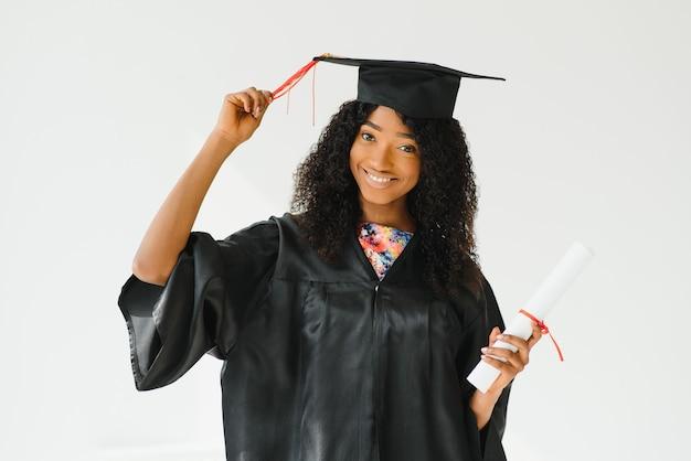 Привлекательная женщина-выпускница афро-американского университета на белом фоне