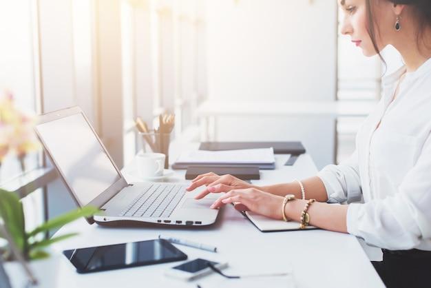 魅力的な女性アシスタントが働いて、タイピングして、ポータブルコンピュータを使って、集中して、モニターを見ています。ビジネスの電子メールを読んでいるサラリーマン。