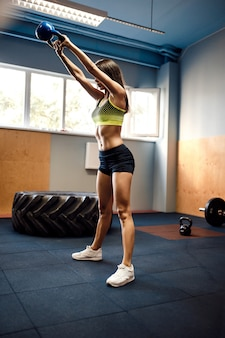 Attractive female athlete performing a kettle-bell swing