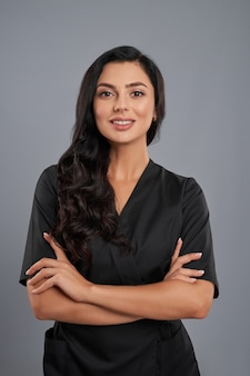 Привлекательная женщина-косметолог в черной униформе, стоя со скрещенными руками на сером фоне.