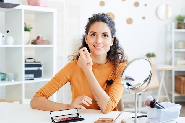 Привлекательная женщина-бьюти-блогер тестирует новые цвета палитры помады, делая образцы на руке