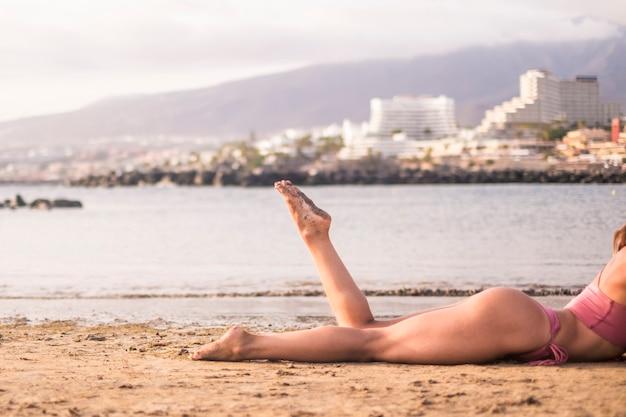 魅力的な女性の体と美しい女性の足は、砂の上で日光浴をしながらビーチでリラックスして横になります。休日の夏休みの概念のための海岸と海。旅行の女の子