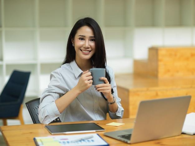 魅力的な女性のビジネスマネージャーは、ラップトップで作業机の前に手でコーヒーマグを保持します。