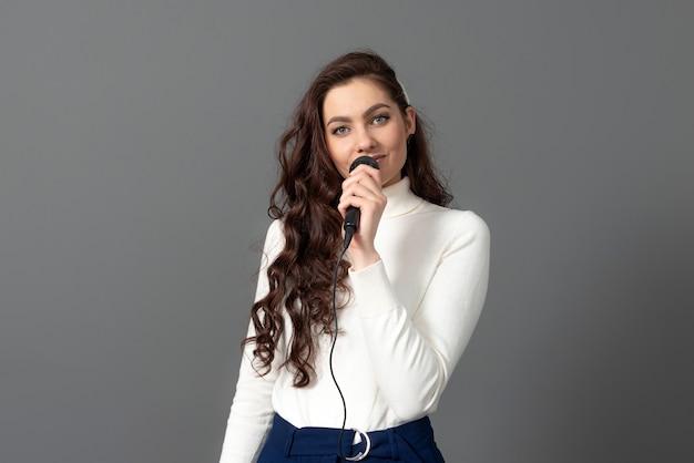 Привлекательная женщина-спикер конференции во время презентации держит микрофон и делает несколько жестов, изолированные на сером