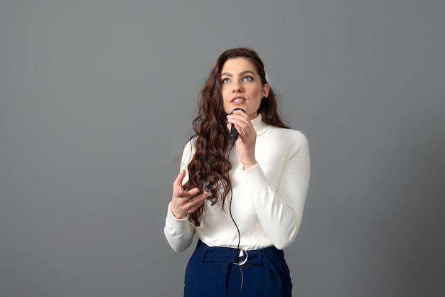 프레젠테이션 중에 매력적인 여성 회의 스피커는 마이크를 보유하고 회색에 고립 된 일부 제스처를 만듭니다.