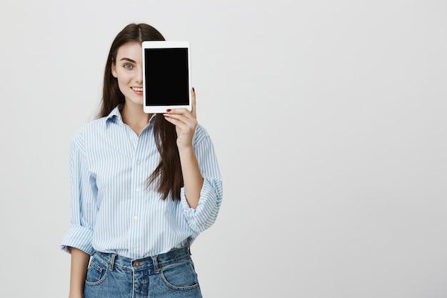 Attraente femmina coprire metà del viso con tavoletta digitale, mostrando il display