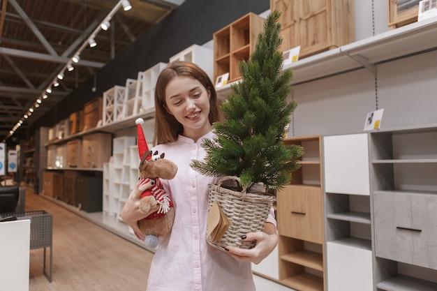 Привлекательная покупательница, несущая рождественскую елку в горшке и игрушку в виде оленей, гуляет в магазине мебели