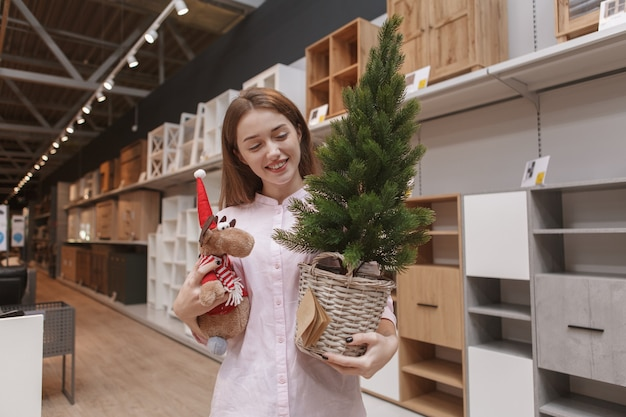 Attractive female customer carrying potted christmas tree and reindeer toy, walking in furnishings store