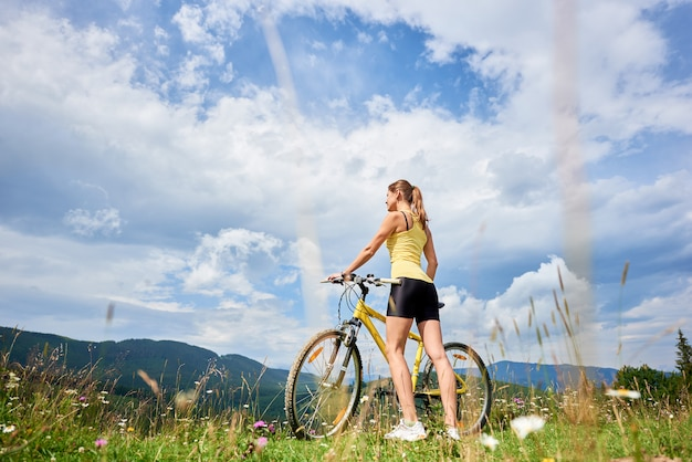 Attractive female cyclist with yellow mountain bicycle, enjoying sunny day in the mountains
