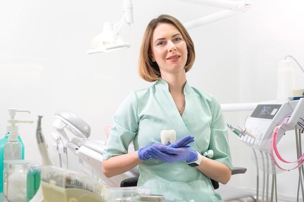 Привлекательная женщина-стоматолог-врач держит фигурку зуба