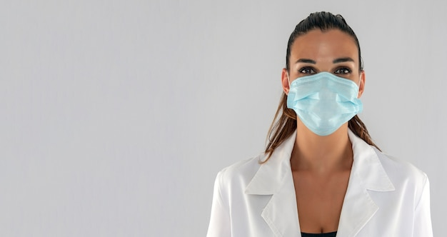 Attractive female doctor with virus protection mask looking straight ahead and white background.