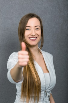 Attractive female doctor woman show thumbs up