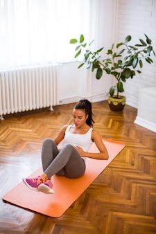 彼女のリビングルームで運動をしている魅力的な女性
