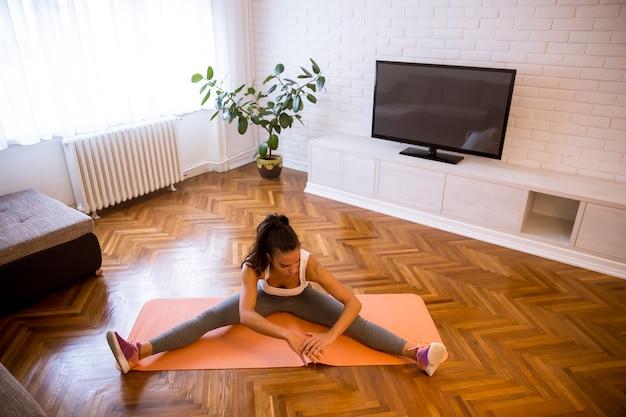 彼女のリビングルームでストレッチ運動を行う魅力的な女性