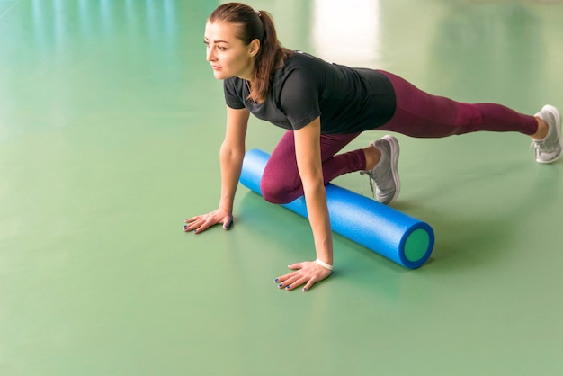 Attractive female exercising pilates fitness doing foam roller exercise and posing in modern bright fitness center