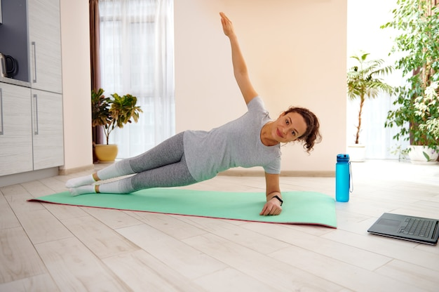自宅のフィットネスマットで板張りの体重運動をしている魅力的な女性のフィットネスインストラクター