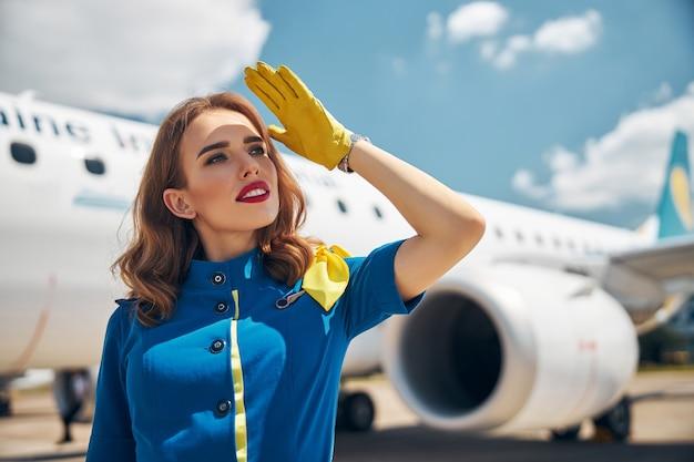 Привлекательная стюардесса в желтых перчатках смотрит в сторону и улыбается, стоя на открытом воздухе с самолетом на заднем плане