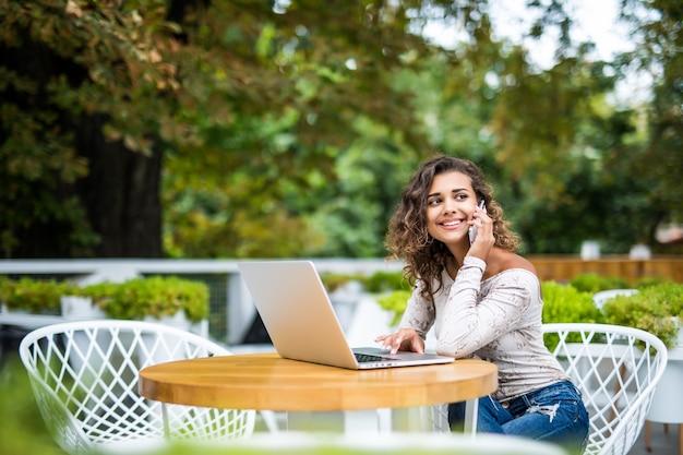 Привлекательная женщина-фрилансер держит смартфон, сидя в современной кофейне