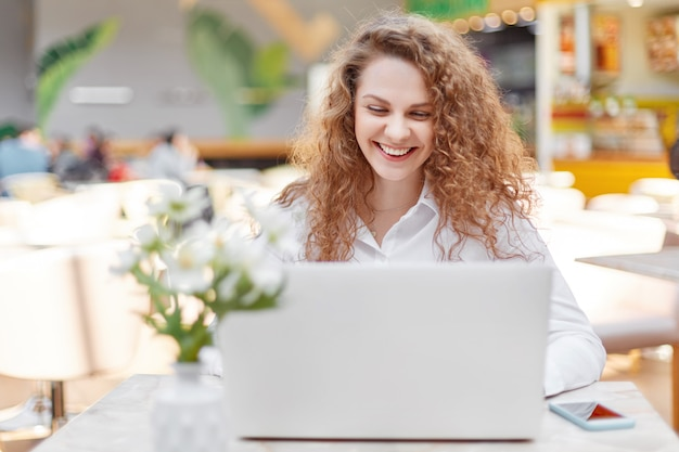 Attractive female freelancer works remotely on portable laptop computer