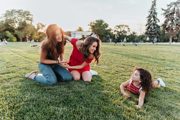 小さな子供と一緒に芝生の上でポーズをとる魅力的な女性の友人。公園で姉妹と時間を過ごすかわいい巻き毛の女の子。