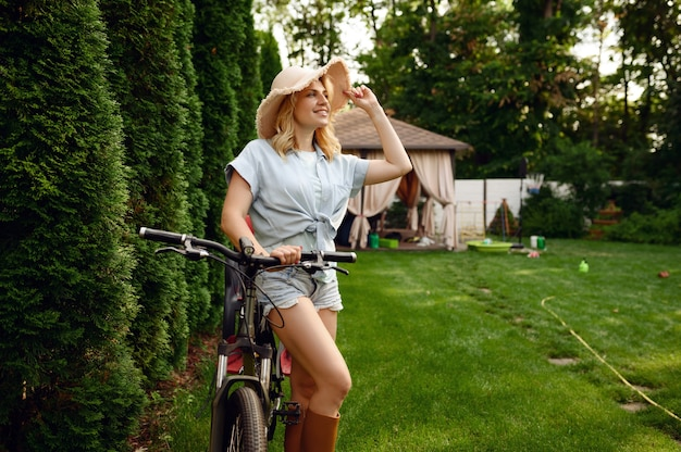 Attractive female gardener poses on bicycle in the garden. woman on cycle outdoor, gardening hobby, florist lifestyle and leisure