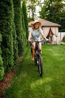 魅力的な女性の庭師が庭で自転車にポーズをとる