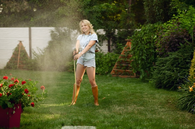 Attractive female gardener with hose watering plants in the garden. woman takes care of flowers outdoor, gardening hobby, florist lifestyle and leisure