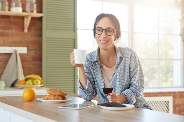 La femmina attraente ha un'espressione felice gode del caffè del mattino con deliziosi croissant dolci e cioccolato