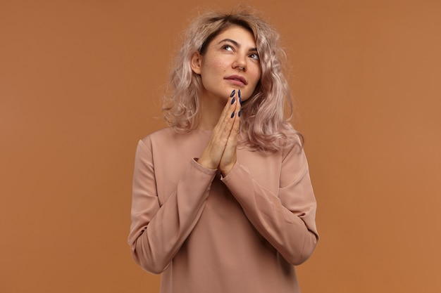 Attractive female hipster pressing hands together and looking up with hopeful smile, praying