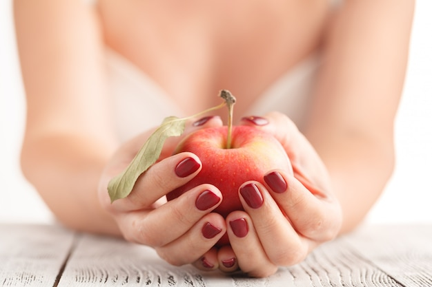 Attractive female holding fruit food apple in manicured hands