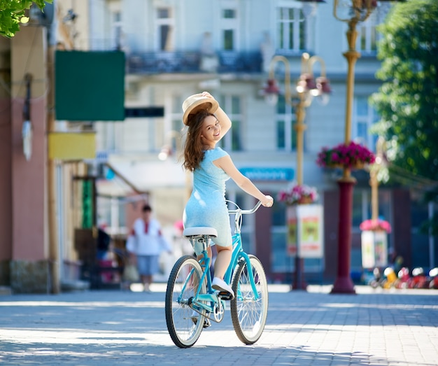 매력적인 여성은 시내 중심에 블루 빈티지 자전거를 타고있는 동안 인사말 기호로 그녀의 모자를 보유