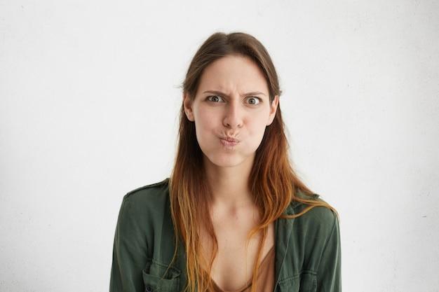 Привлекательная женщина в зеленой повседневной одежде дуется. раздраженная женщина с гримасой смотрела.