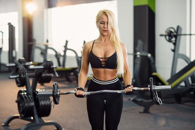 현대 체육관에서 바벨과 팔뚝 운동을하고 스포츠 착용에 매력적인 여성. 스포티하고 건강한 개념.