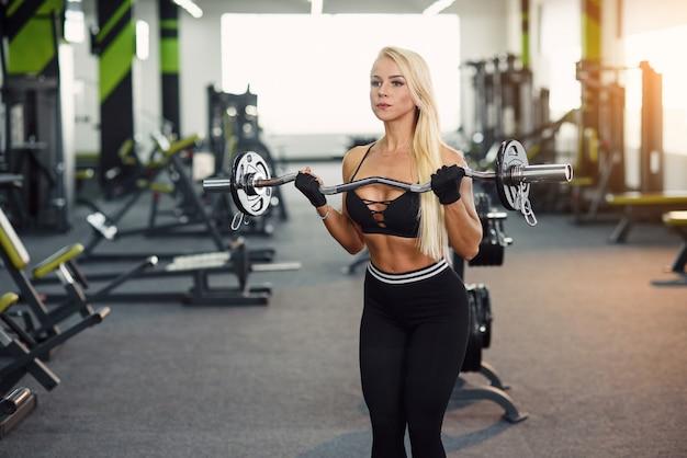 モダンなジムでバーベルで上腕二頭筋運動を行うスポーツウェアの魅力的な女性。スポーティで健康的なコンセプト。