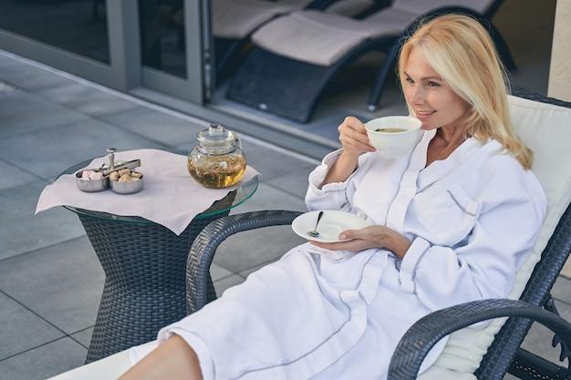 아침에 차를 마시는 동안 흰색 부드러운 목욕 가운에 매력적인 여성