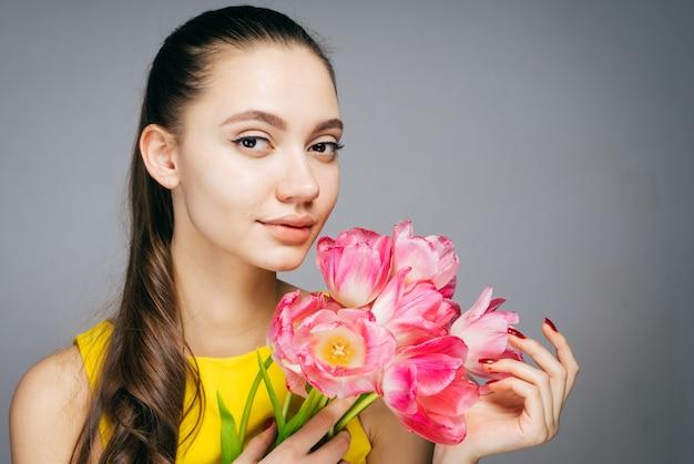 노란 드레스를 입은 매력적인 여성은 향기로운 분홍색 꽃과 미소의 꽃다발을 들고 있습니다