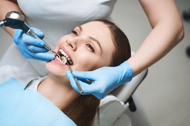 Привлекательная женщина посещает стоматолога и получает лечение корневого канала у специалиста с современным оборудованием.