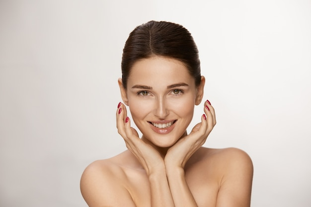 Attractive female looking to camera with smile on white, copy space, gorgeous woman holding arms near face