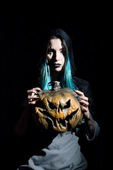 Attractive female magician holding creepy pumpkin