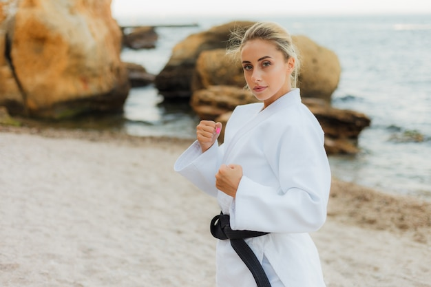 Привлекательная женщина-боевой мастер в белом кимоно с черным поясом стоит в боевой стойке на диком пляже