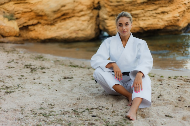 Привлекательная женщина-мастер боевых искусств в белом кимоно с черным поясом сидит на песчаном диком пляже