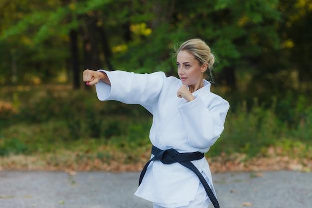 Привлекательная женщина мастер-боец в белом кимоно с черным поясом наносит удар рукой на открытом воздухе