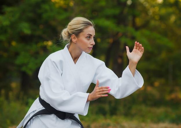 Привлекательная женщина-мастер-боец в белом кимоно с черным поясом стоит в боевой стойке на открытом воздухе